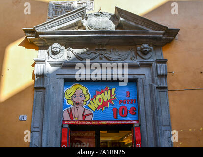 Close-up of an ancient stone door frame and tympanum with a shop sign in pop art style in the historical centre of Lucca, Tuscany, Italy - Stock Photo