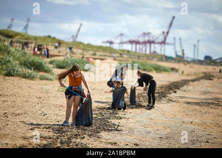 Young teens picking up plastic waste on the beach  at  Waterloo Crosby Beach, Liverpool
