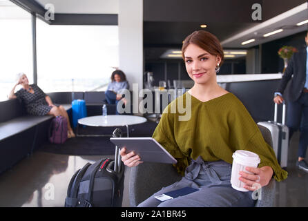 Millennial female traveller with coffee sitting in modern airport terminal holding tablet looking at camera