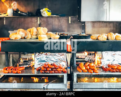 Christmas market in Germany, Europe. Traditional bratwurst sausages and bread on grill during outdoor seasonal Christmas market in Munich - Stock Photo