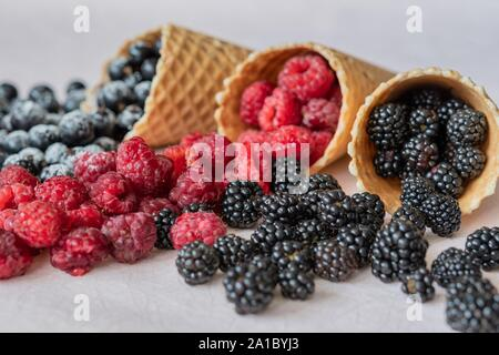 Three waffle cones close-up of which poured on the table raspberries, currants, blackberries in powdered sugar - Stock Photo