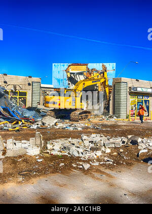 Demolition of a store building by a tracked vehicle in downtown Tucson Arizona - Stock Photo