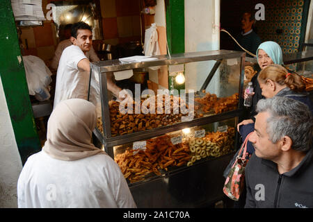 A food merchant selling sweets, biscuits and pastries serves waiting customers in the market of the kasbah, in the medina of Tunis, Tunisia. - Stock Photo