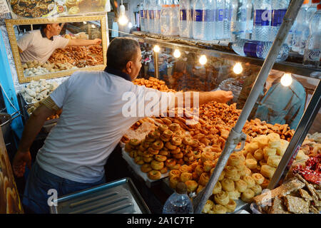 A food merchant selling biscuits and pastries serves a waiting customer in the market of the kasbah, in the medina of Tunis, Tunisia. - Stock Photo