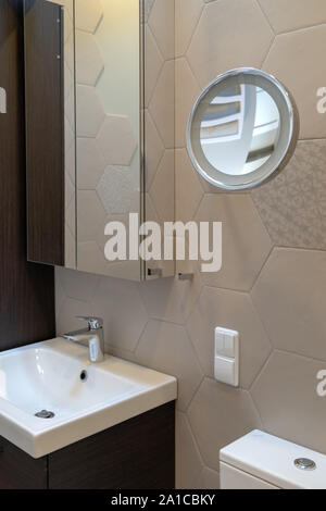 Part of the bathroom in a private house. Cabinet on tile wall with mirror. Below sink with faucet. Wall mounted round special magnifying mirror - Stock Photo