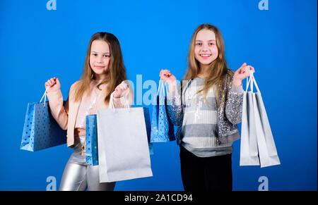 Happy children. Little girl sisters. Sales and discounts. Sisterhood and family. savings on purchases. Kid fashion. Blue background. Small girls with shopping bags. Happy childrens day. happy shop. - Stock Photo