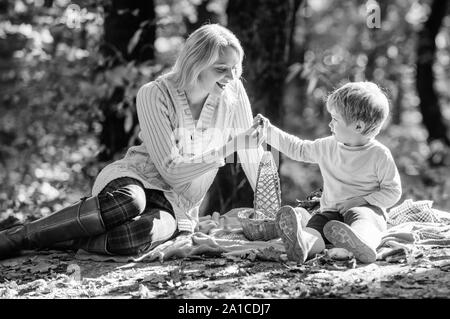 Explore nature together. Mom and kid boy relaxing while hiking in forest. Family picnic. Mother pretty woman and little son sit on plaid relaxing forest picnic. Good day for spring picnic in nature. - Stock Photo