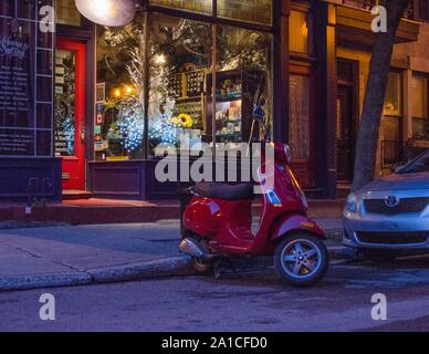 A red Vespa scooter outside a Montreal shop on a summer evening. - Stock Photo