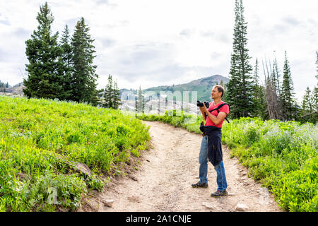 Albion Basin, Utah summer with man taking pictures of landscape view of dirt road trail up in Wasatch mountains to Cecret Lake - Stock Photo