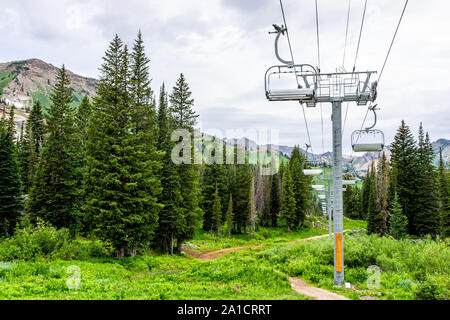 Albion Basin, Utah summer with ski lift chairs on cables and cloudy sky in rocky Wasatch mountains on trail - Stock Photo