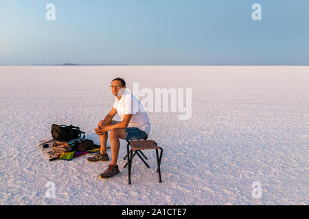 Bonneville Salt Flats near Salt Lake City, Utah at twilight after sunset with purple salt and man sitting watching view with horizon - Stock Photo