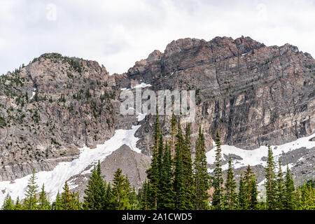 Albion Basin, Utah view of green pine trees on summer trail in 2019 in Wasatch mountains with rocky snowy Devil's Castle mountain - Stock Photo