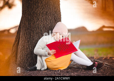 Little caucasian girl is reading the book under the fall tree - Stock Photo