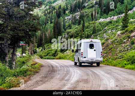 Alta, USA - July 27, 2019: Albion Basin, Utah summer with shuttle bus on dirt road in summer in Wasatch mountains - Stock Photo
