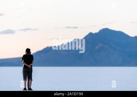 Wendover, USA - July 27, 2019: People couple hugging on white Bonneville Salt Flats near Salt Lake City, Utah and silhouette mountain view - Stock Photo