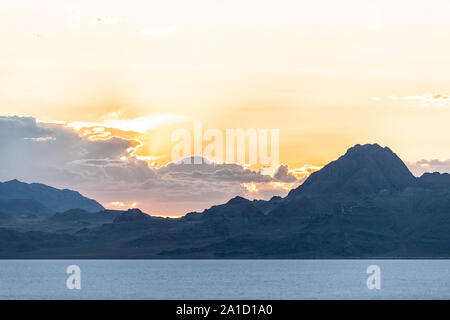 Bonneville Salt Flats landscape near Salt Lake City, Utah and silhouette mountain view and sunset behind clouds - Stock Photo