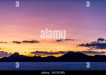 Bonneville Salt Flats colorful purple dark twilight silhouette mountain view after sunset near Salt Lake City, Utah with clouds - Stock Photo