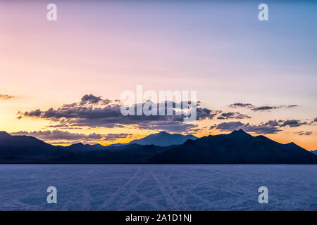 Bonneville Salt Flats colorful purple dark twilight silhouette mountain panoramic view after sunset near Salt Lake City, Utah with clouds - Stock Photo