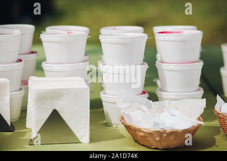 Soup in containers on table.Stacks of white plastic containers of red soup or borsch prepared for takeaway service on table with green tablecloth. - Stock Photo