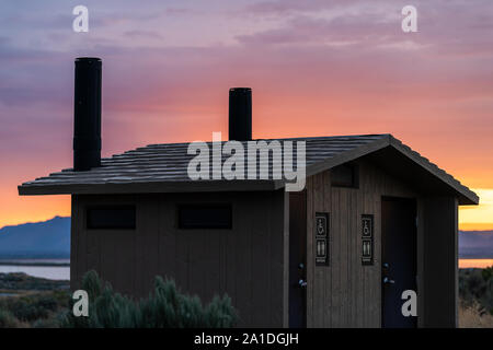 Sunrise on Great Salt Lake in Antelope Island State Park from Ladyfinger campground in Utah with restroom bathroom cabin building and sign - Stock Photo