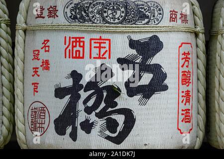 Barrrel of sake at Meiji shrine in Harajuku, Tokyo, Japan. Barrels of sake wrapped in straw. - Stock Photo