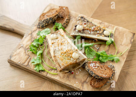 Beef bone marrow with chimichurri sauce and toasted bun. Served on a chopping wooden Board. Menu BBQ restaurant - Stock Photo
