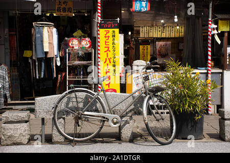 TOKYO, JAPAN - MARCH 31 : Japanese people stopping classic retro vintage old bicycle with basket at front of Local souvenir gift shop in Narita old to - Stock Photo