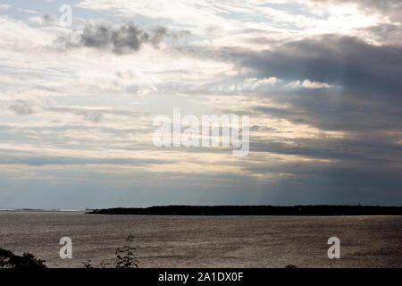 The setting sun filters through the clouds as seen from Mackinac Island, Michigan. - Stock Photo