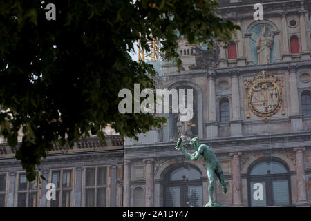 Statue of Silvius Brabo, slayer of Druon Antigoon, in the Grote Markt with the Antwerp City Hall (Antwerpen Stadhuis) in the background. - Stock Photo
