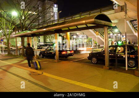 Japanese people driving taxi stop waiting traveler and passenger use service at bus station in night time at Narita town of Chiba Prefecture on March - Stock Photo