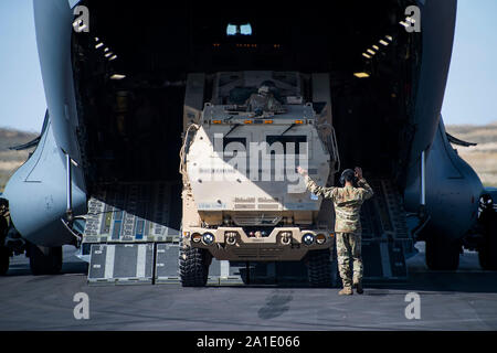 U.S. Air Force Senior Airman Shaheem Osborne, right, 21st Airlift Squadron C-17 Globemaster III loadmaster, 60th Air Mobility Wing, Travis Air Force Base, California, guides a U.S. Army High Mobility Artillery Rocket System (HIMARS) in preparation for a HIMARS Rapid Infiltration (HI-RAIN) training mission during Exercise Mobility Guardian 2019, Selah Creek Landing Zone, Washington, Sept. 25, 2019. Exercise Mobility Guardian is Air Mobility Command's premier, large scale mobility exercise. Through robust and relevant training, Mobility Guardian improves the readiness and capabilities of Mobilit - Stock Photo