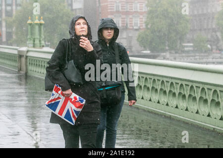 London, United Kingdom - 26 September 2019. Pedestrians brave the heavy rain showers on Westminster Bridge. Credit: amer ghazzal/Alamy Live News - Stock Photo