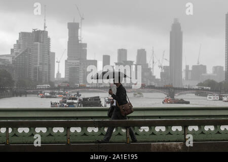 London, United Kingdom - 26 September 2019. Pedestrians with umbrellas brave the heavy rain showers on Westminster Bridge. Credit: amer ghazzal/Alamy Live News - Stock Photo