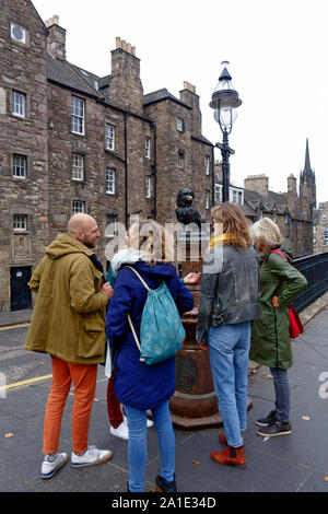 Tourists looking at the Greyfriars Bobby statue at the corner of Candlemaker Row and George IV Bridge in Edinburgh, Scotland - Stock Photo