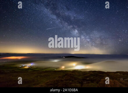 Dramatic sea mist rolls in over local farms at night with the Milky Way overhead on the Lleyn Peninsula in North Wales seen from Uwchmynydd. - Stock Photo