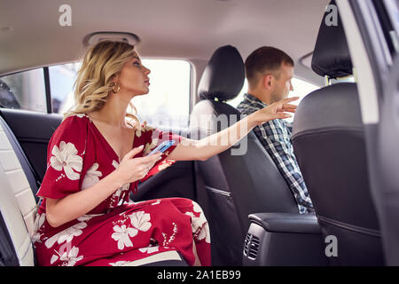 Image of blonde woman looking at camera sitting in back seat of car during day - Stock Photo