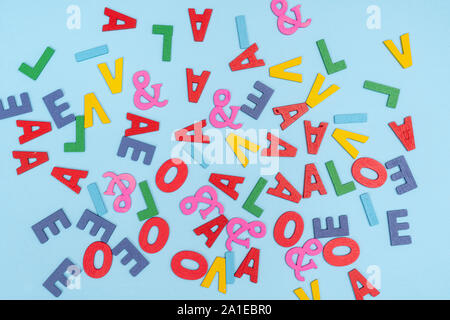 some letters of the colorful alphabet in scattered order on a colored surface - Stock Photo