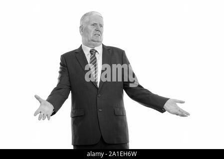 Studio shot of thoughtful mature businessman looking confused while looking at distance - Stock Photo