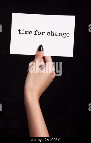 hand holding white card on black background - time for change - Stock Photo
