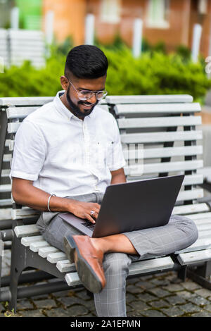 Happy indian businessman sitting on bench with laptop - Stock Photo