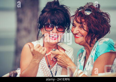 Image of a two happy senior women friends sitting in cafe talking with each other drinking coffee, pointing fingers to someone. - Stock Photo