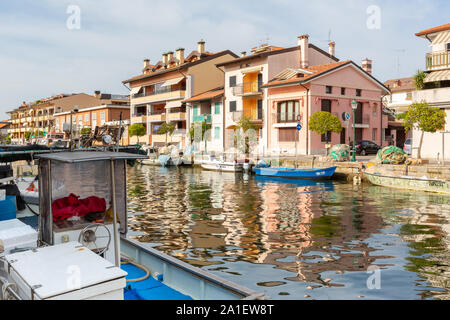 JULY 22, 2019 - GRADO, ITALY - Colored residential buildings and boats in the sunset light are mirror reflected in sea water of the harbor of Grado - Stock Photo