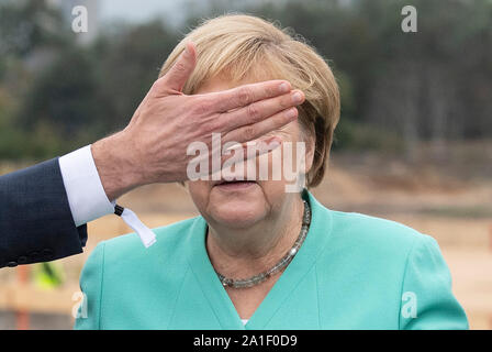 26 September 2019, Hessen, Frankfurt/Main: Federal Chancellor Angela Merkel (CDU) follows the statements of a DFB official at the laying of the foundation stone of the DFB Academy. The face of the Chancellor is partially covered by his hand. Photo: Boris Roessler/dpa - Stock Photo