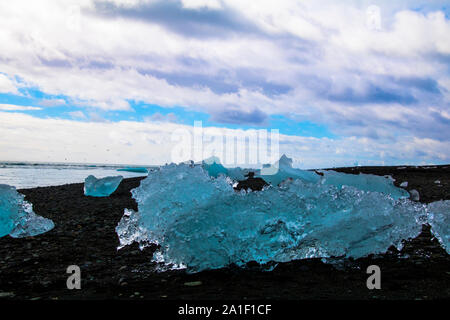 Ice floe on a black sand beach with sea and cloudy sky in the background. Photographed in the lagoon of Jökulsarlon in the south of Iceland - Stock Photo