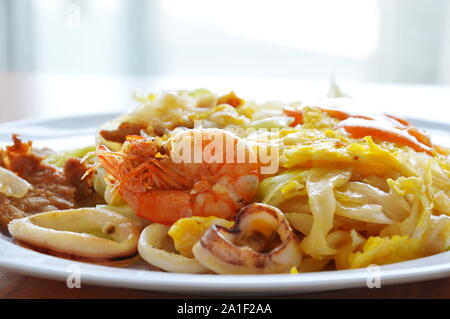 stir fried rice noodle seafood and cabbage dressing chili sauce on dish - Stock Photo