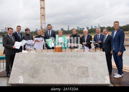 26 September 2019, Hessen, Frankfurt/Main: Federal Chancellor Agela Merkel (M, CDU) stands with representatives from sport and politics at the laying of the foundation stone of the DFB Academy. Photo: Boris Roessler/dpa - Stock Photo