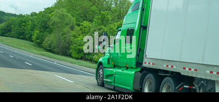 Truck green color with white trailer on the highway, cloudy sky, closeup side view. USA countryside - Stock Photo