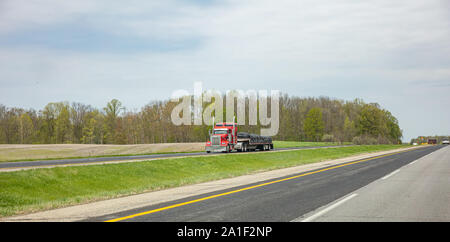 Truck red color with trailer on the highway, cloudy sky, USA countryside - Stock Photo