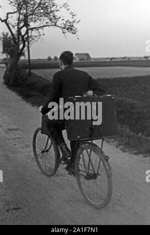 Pfarrer Egon Vögler mit dem Fahrrad unterwegs in seiner Gemeinde Horka, Deutschland 1949. Priest Egon Voegler on his bicycle at Horka, Germany 1949. - Stock Photo
