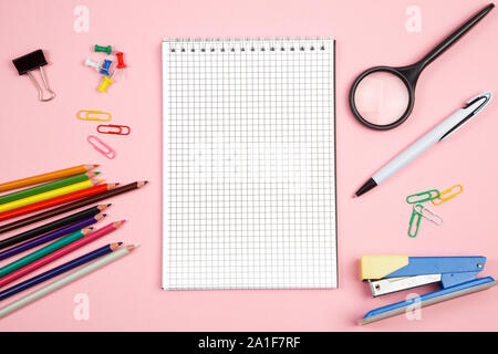 colored pencils, stationery, paper notebook with pen and magnifier on pink isolated background. top view. flat lay. mockup - Stock Photo